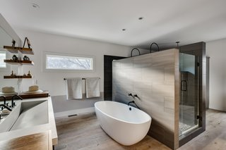 This Boulder Home's Unique Bedroom-Bathroom Puts a New Twist on the Open Plan - Photo 7 of 8 - Glenrock tiles in light grey provide dramatic contrast against the freestanding tub by Victoria + Albert. Juilland used the same tiles, though in a darker shade, on the inside of the shower.