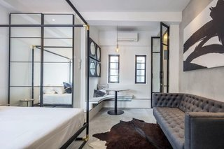 Experience a Modern, Eclectic Side of Singapore at One of These 10 City Stays - Photo 7 of 13 - Located in a 1939 estate, this art deco-inspired, one-bedroom apartment is equipped with a queen-sized bed, workspace, sofa, and a kitchenette with a microwave and refrigerator.