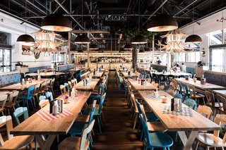 10 Brewpubs That Have Tapped the Art of Modern Design - Photo 6 of 12 - Located in a former goods shed, Munich Brauhaus can hold 900 guests, many of which can gather in the main dining space that's filled with long communal tables—a brauhaus necessity.