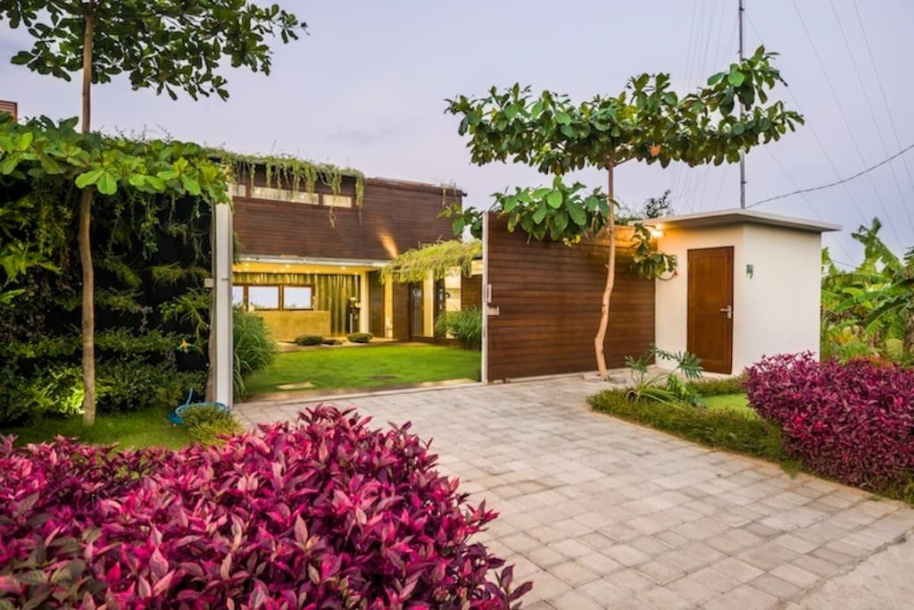 Located in a peaceful residential area about 500 meters from the ocean and surrounded by lush paddy fields, this three bedroom house is made out of shipping containers and has a unique sunken outdoor conversation pit that's perfect for cocktails in the evenings.  Photo 7 of 11 in Connect With Bali's Tropical Landscape at One of these Modern Villas