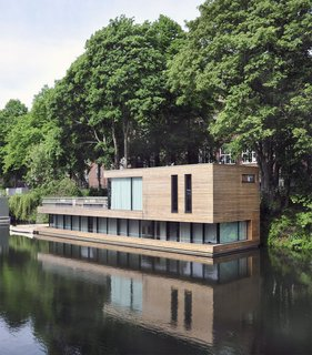 10 Modern Floating Homes That Offer an Aquatic Lifestyle - Photo 1 of 10 - In Hamberg, Germany, Houseboat on the Eilbekkanal is enveloped in sliding timber slats, creating a constant connection between the interior and the exterior.