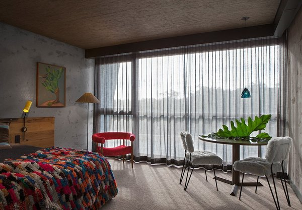 Located in the Nishi Residential Building in Canberra, Australia, Hotel Hotel was designed by Sydney-based filmmaker Don Cameron, who used restored 20th-century furnishings and bespoke joinery made with reclaimed oak to create unique and cozy guest rooms.