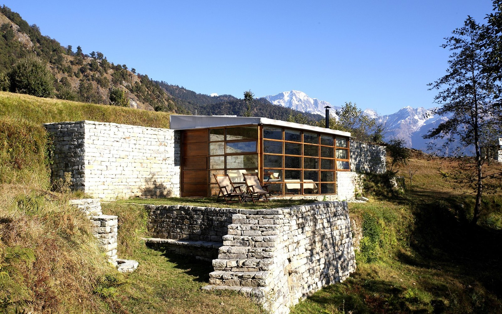 Enjoy fresh mountain air and get a bird's eye view of the Himalayas at Shakti 360º Leti – four private stone, glass and wood cabins high on the peaks of the India-Nepal border. Tagged: Outdoor, Trees, Slope, and Grass.  Photo 6 of 13 in Hide Out in One of These Asian Retreats That Are Immersed in Nature
