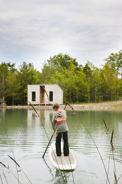 Cooper, 11,  paddleboards toward an outbuilding that contains a sauna.