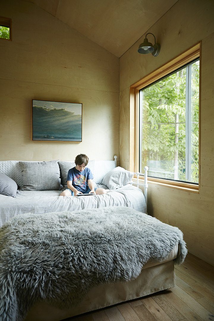 Emerson, 8, reads in a sitting room where overnight guests stay.  The Land House by Dwell from Hot to Trot