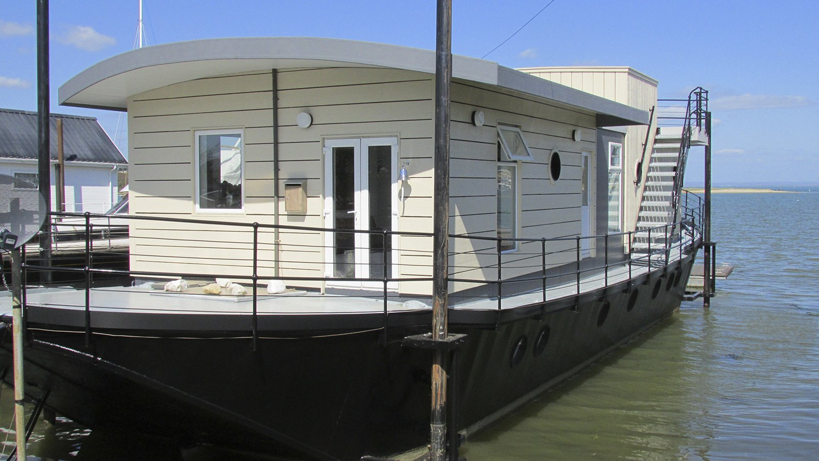 The Harbour Houseboat, which offers stunning views across Bembridge Harbour in Isle Of Wight has a commodious open-plan living lounge and kitchen, and warmly furnished rooms with plush Loaf beds.