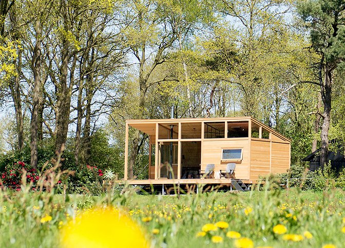 Surrounded by forests and meadows, this modern, minimalist cabin in Lettele, Netherlands is a prefab project by Dutch designers owners and designers Arno Schuurs and Paulien van Noort. The smart and sustainable layout incorporates large windows that bring the outdoors in. Materials such as untreated Oregon pine planks, oak fishbone flooring, concrete and raw steel were used to keep construction footprint low.