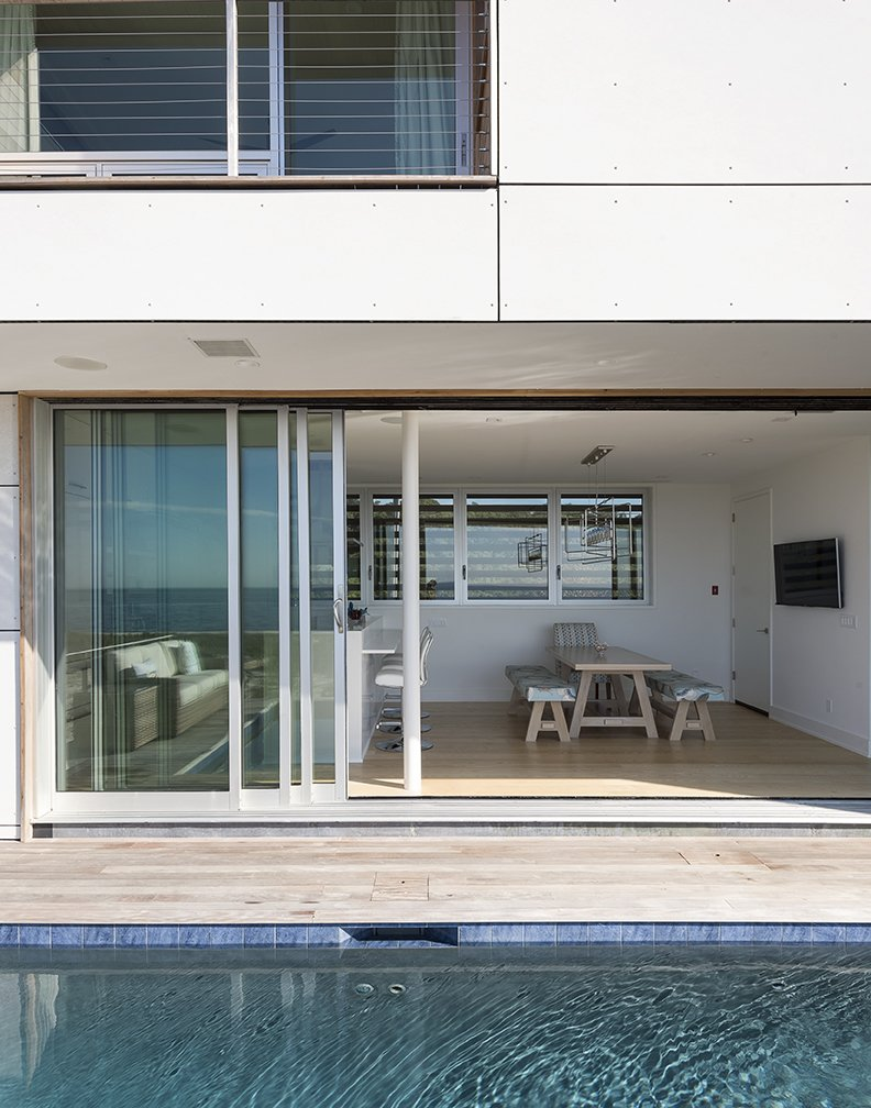 Having a strong outdoor element was also important.  A 32-foot-wide Solar Innovations sliding door connects the kitchen  to a deck and pool.  Photo 9 of 14 in Shore Bet
