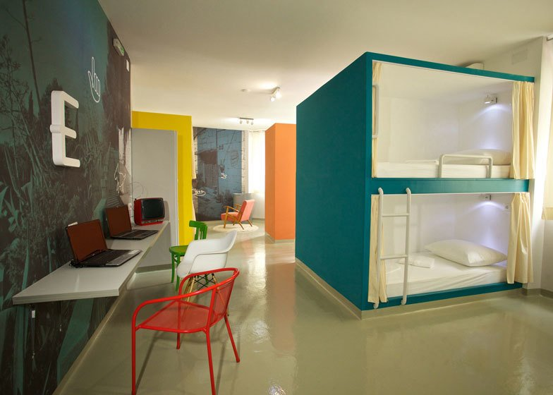 Two more units are located in a petite white room with an extra bed raised high above the flooring, resting atop stacked lockers.