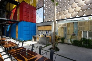 Stacked shipping containers—painted red, blue, and yellow to distinguish the different room types—are arranged around a large socializing area for guests.