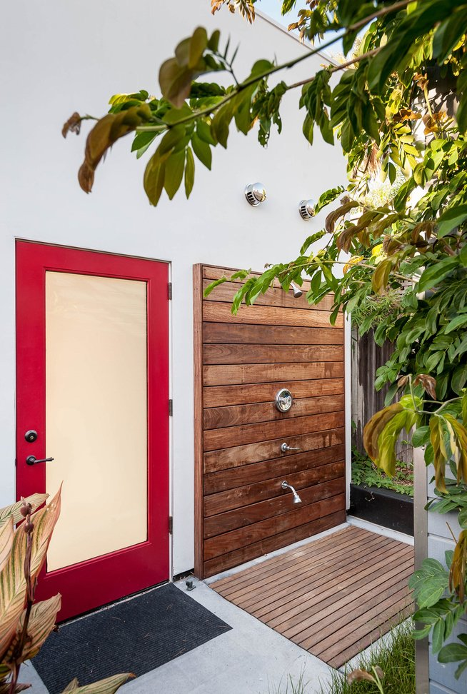 "Designed for easy beachside living, ""the cube"" in the backyard—essentially the renovated garage—sports a sleek outdoor shower complete with a teak deck and Moen fixtures."