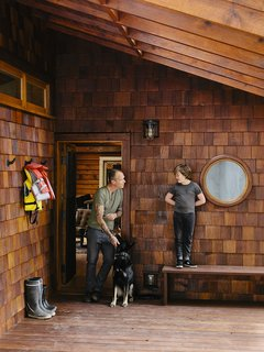 An Eclectic Pacific Northwest Cottage - Photo 1 of 13 - At the entrance, Bruce is joined by his son, Sozé, and dog, Izzy. The 1940s shingled cottage was renovated by architectural designer Randall Recinos, designer Brian Paquette, and contractor Dylan Conrad.