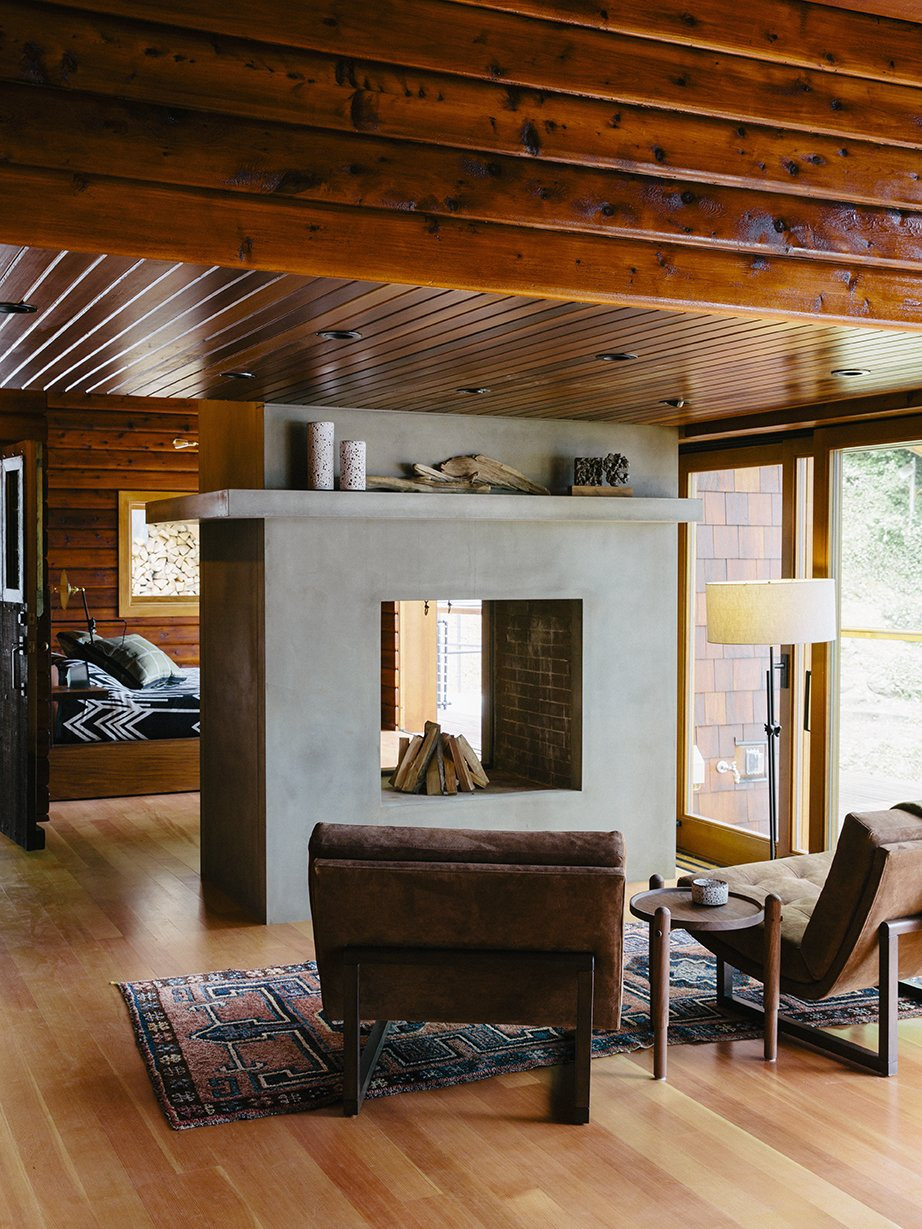 Bruce Livingstone's seaside getaway in British Columbia features a remarkably open layout. The master bedroom flows into the living room, where Griffin lounge chairs by Lawson-Fenning face a fireplace clad in glass fiber–reinforced concrete panels by Wiersma Masonry. Tagged: Living Room, Two-Sided Fireplace, and Light Hardwood Floor. An Eclectic Pacific Northwest Cottage - Photo 2 of 13
