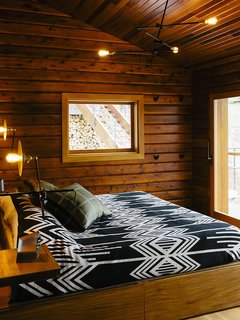 An Eclectic Pacific Northwest Cottage - Photo 3 of 13 - The master bedroom's <br>custom bed has built-in storage. The lighting is by Workstead.