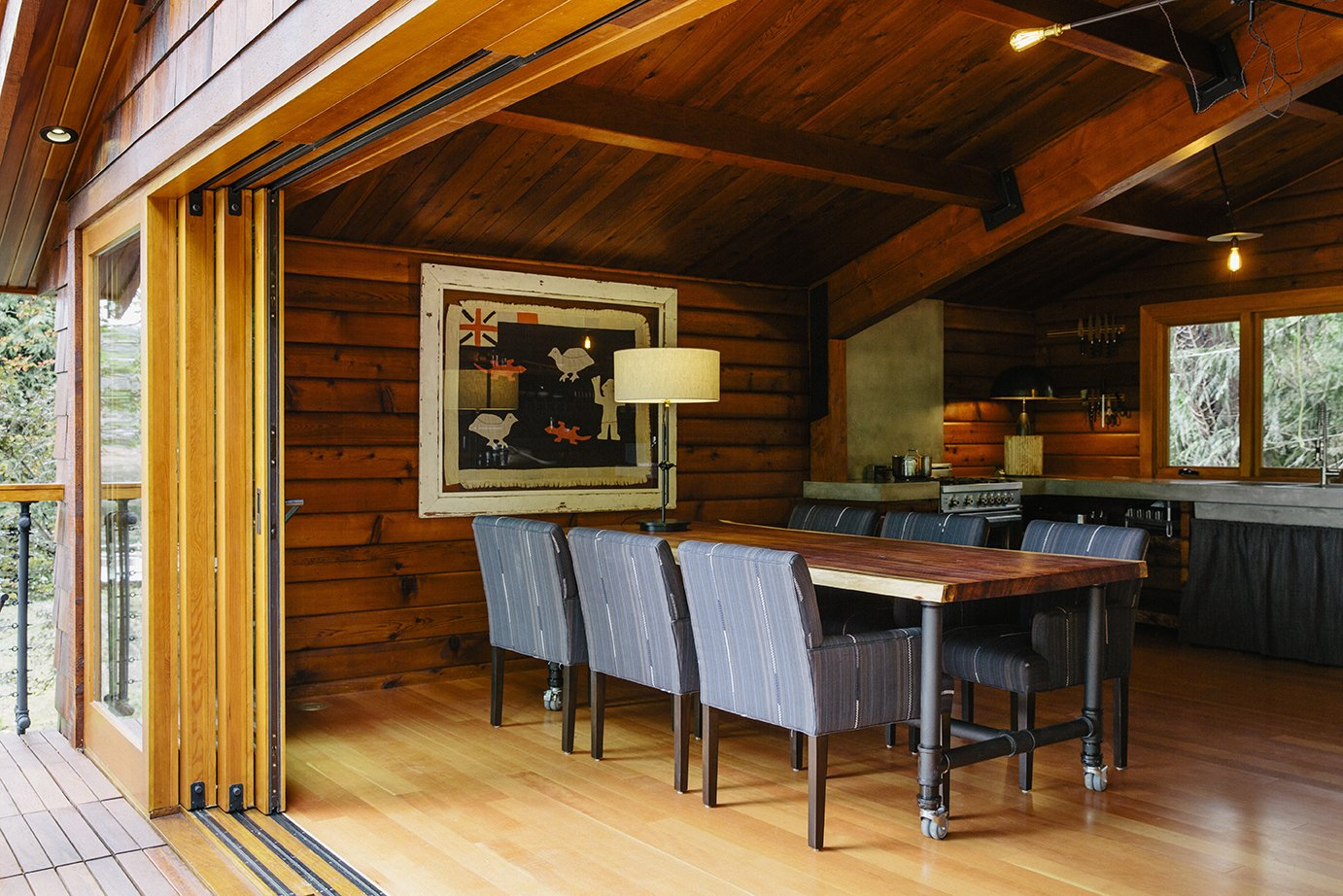 On the main floor, custom sliders by Oakridge Windows & Doors open to a table and chairs designed by Paquette and built by Conrad Contracting. The wood paneling on the walls was salvaged from the original structure and resawn; each piece was scuffed with fine sandpaper and coated with Projectol.  Photo 4 of 13 in An Eclectic Pacific Northwest Cottage
