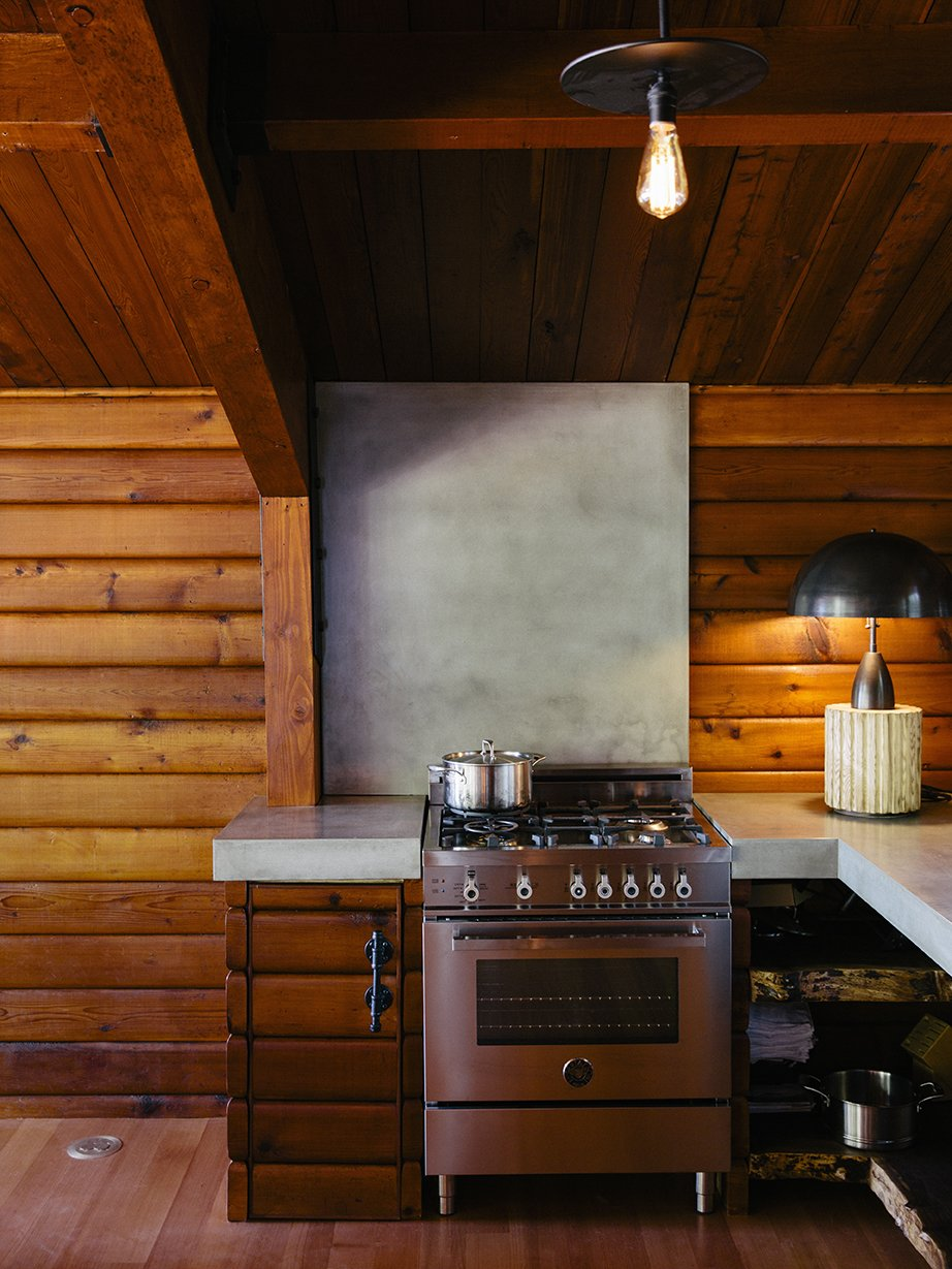 A Column lamp by Apparatus and concrete countertops join a Bertazzoni propane range. The brass pendant is by Workstead. Tagged: Kitchen, Wood Cabinet, Concrete Counter, Range, Ceiling Lighting, and Table Lighting.  Photo 5 of 13 in An Eclectic Pacific Northwest Cottage