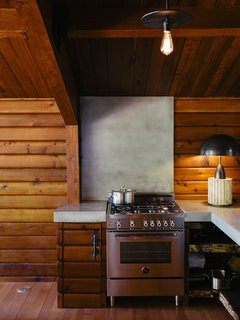 An Eclectic Pacific Northwest Cottage - Photo 5 of 13 - A Column lamp by Apparatus and concrete countertops join a Bertazzoni propane range. The brass pendant<br>is by Workstead.