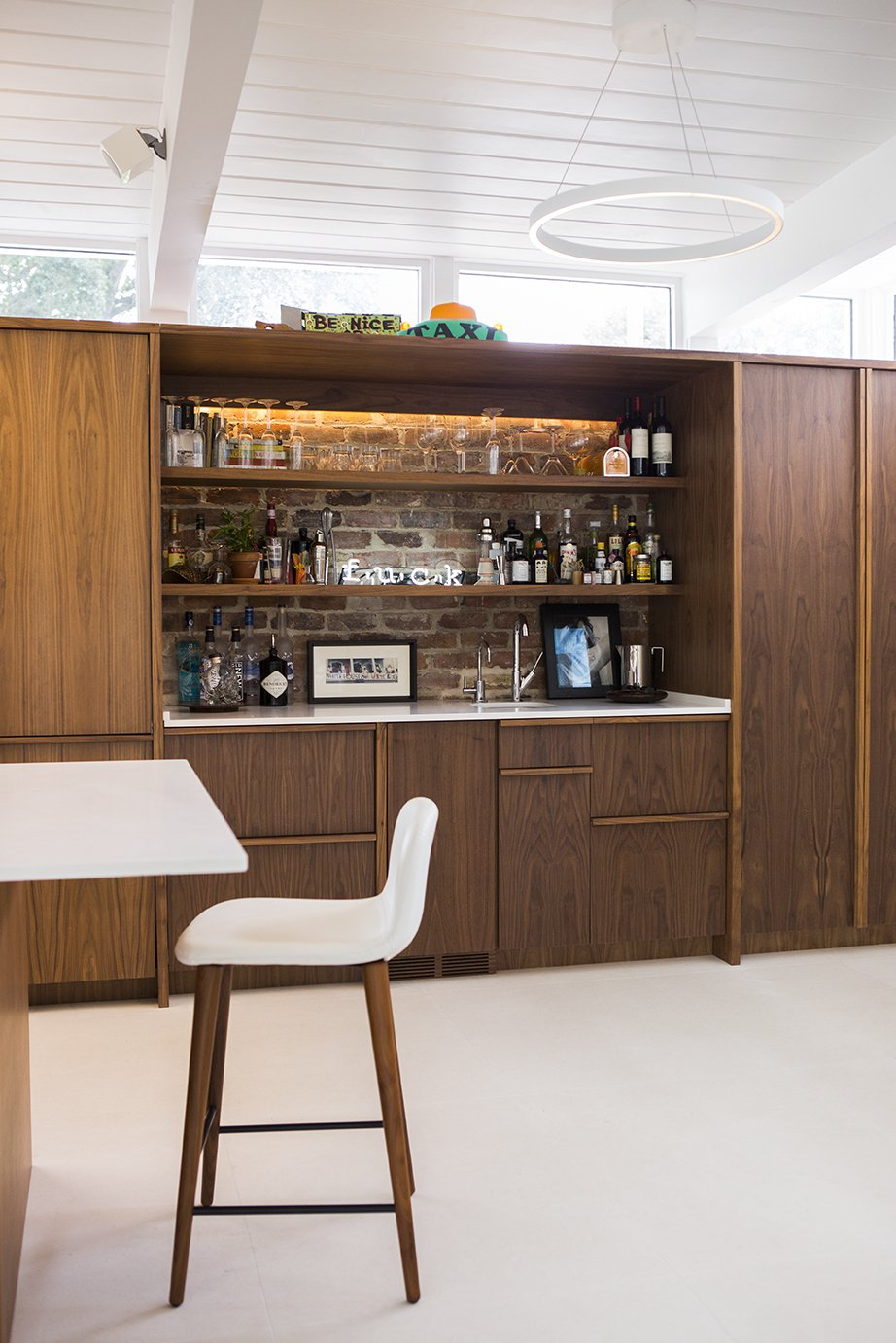 The kitchen and bar millwork is ApplePly with a walnut veneer. Tagged: Dining Room, Bar, Chair, Table, and Ceiling Lighting.  Emerald Street Residence by Dwell from Back to the Garden
