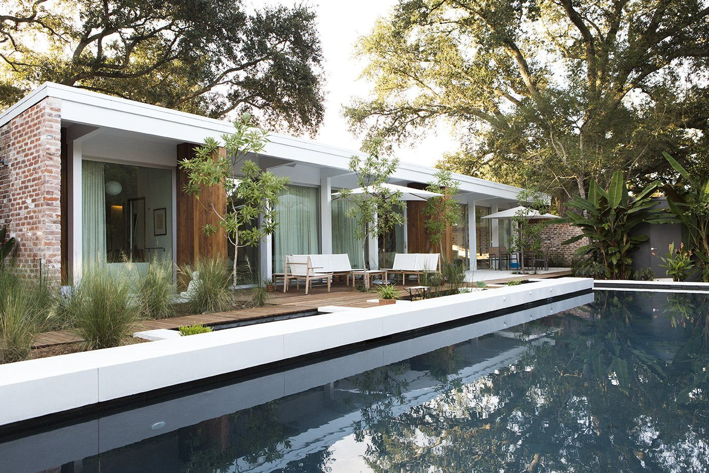 To revive the original architects' vision, studioWTA restored a four-foot roof overhang above a wall of La Cantina sliders. The shade helps limit solar gain, while a pool by Evans + Lighter Landscape Architecture provides respite on sweltering summer days. Tagged: Outdoor, Large Pools, Tubs, Shower, Swimming Pools, Tubs, Shower, Large Patio, Porch, Deck, and Wood Patio, Porch, Deck.  Emerald Street Residence by Dwell from Back to the Garden