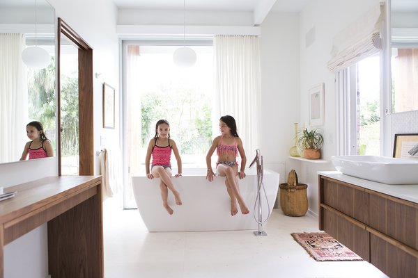 In the master bathroom, a BainUltra Essencia freestanding tub with an Axor Starck filler offers a perch for the couple's granddaughter Arabella and her cousin Alexandra. The built-in vanity is made of the same ApplePly material as the kitchen cabinetry.