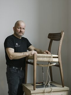 Warp Speed - Photo 2 of 12 - Master weaver Benny Hammer Larsen has worked for Danish furniture company Carl Hansen <br>& Søn for more than two decades. He travels the globe, demonstrating the meticulous techniques used to realize each piece. He stands next to the reintroduced CH23 dining chair, by Hans J. Wegner.