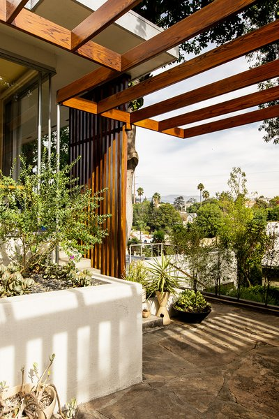 Andrew worked with contractor Miguel Perez to rebuild the home's redwood trellis, matching the stain to the adjoining slat screen, which is original.  Photo 7 of The Romano-Ferrer Residence modern home