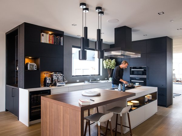 The black steel A110 pendants by Alvar Aalto match the Poliform ventilation hood and ebonized white oak  cabinets by Leicht Haus. LED  lighting is integrated into the island shelving. The drawers underneath are handleless and open electronically by touch using a servo drive.