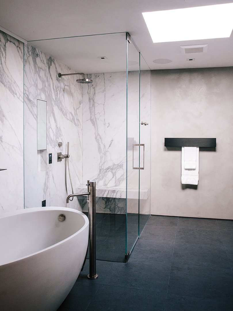 In the master bathroom, a freestanding Waterworks tub is paired with a Fantini fixture. Calacatta marble surrounds the shower; the flooring is Evolution ceramic tile from Apavisa. Tagged: Bath Room, Marble Wall, Ceramic Tile Floor, Freestanding Tub, and Enclosed Shower.  Photo 7 of 15 in Domino Effect: How a Bedroom Refresh Jump-Started a Whole-House Remodel For a Tech Exec
