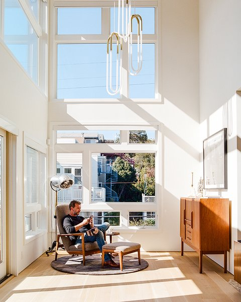 Tom and Kate own the top two  floors of the building. On the lower level, in the double-height foyer, Milo Baughman's Recliner 74 is positioned beneath Rudi Double Loop pendants by Lukas Peet for Roll & Hill. The floor lamp is a custom piece that De Angelis Designs adapted from a vintage salon hood dryer.
