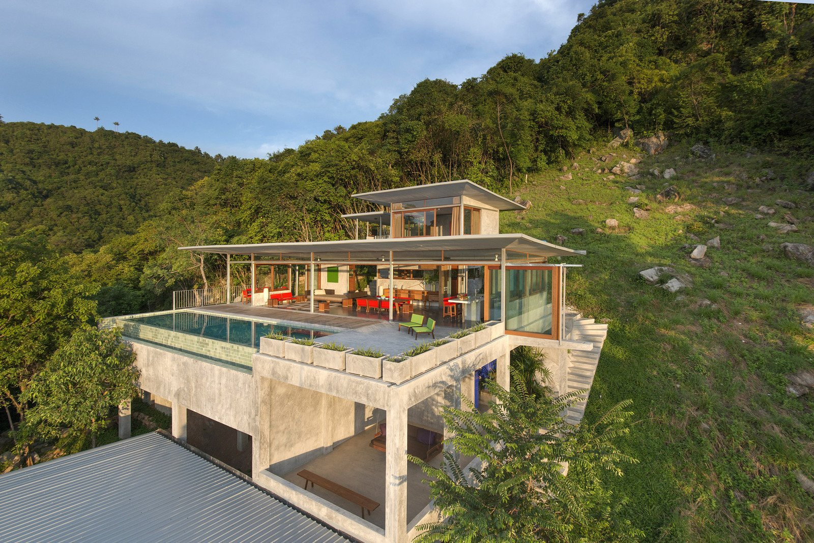 Tagged: Infinity Pools, Tubs, Shower, Wood Patio, Porch, Deck, Concrete Patio, Porch, Deck, Trees, Back Yard, Exterior, Concrete Siding Material, and House.  Photo 2 of 11 in Take a Trip to This Photographer-Designed Concrete Home in Thailand