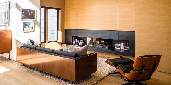 Modern home with living room, ribbon fireplace, ottomans, chair, gas burning fireplace, light hardwood floor, and sofa. Photo  of Conrad Residence