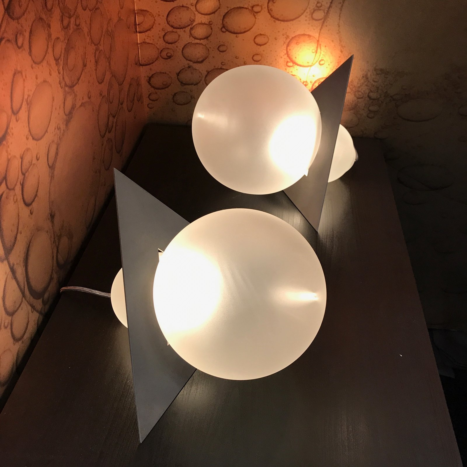 Portland-based glassblowing masters Esque partnered with designer Harry Allen on Liaison, lighting pieces made of sand-blasted glass and stainless steel. The wall covering in the background is by Flavor Paper, frequent collaborators of Esque's.