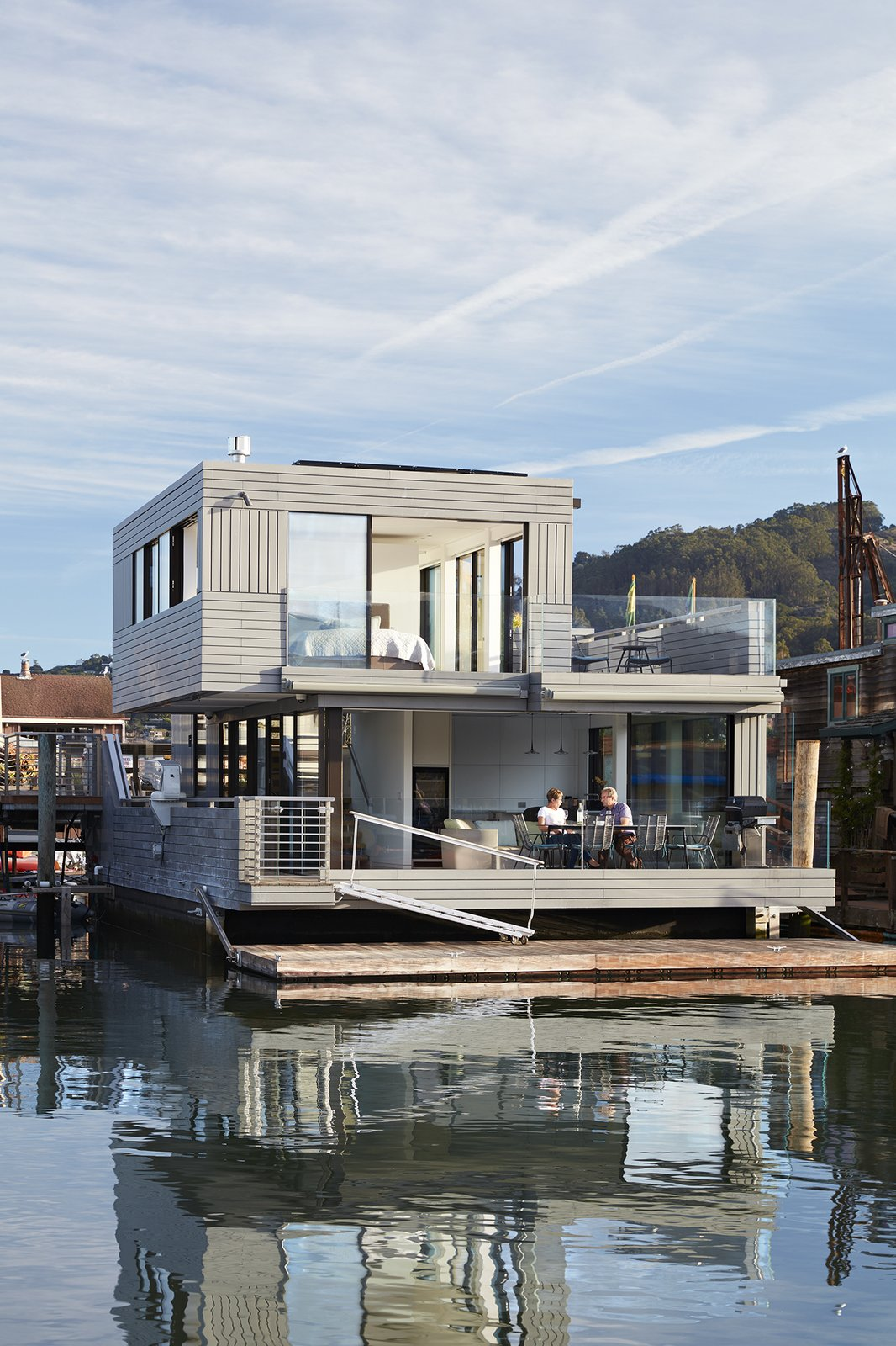 Automatic retractable Sky-Frame windows open the living room  completely on two sides. Tagged: Large Patio, Porch, Deck, Hanging Lighting, and Outdoor.  Floating Dreams Residence by Dwell from Water Sports