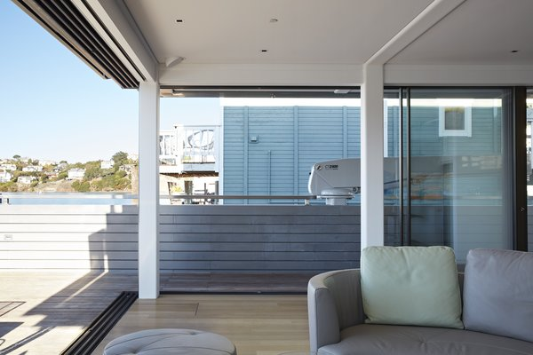 Modern home with large patio, porch, deck, hanging lighting, and living room. A touch of a button summons the bar from its berth in the lower level, where the home theater also resides when not in use; the systems are custom installations by Classic Innovations. Photo 4 of Floating Dreams Residence