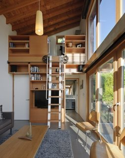 The double-height interior features an upper loft accessed by a custom wood-and-aluminum rolling ladder.