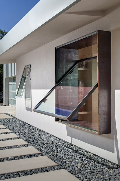 A custom rain-gutter system collects even slight amounts of precipitation in an underground cistern and distributes it to the yard. The Cor-Ten pivoting window is by Brian Linn of Vincent Designs.