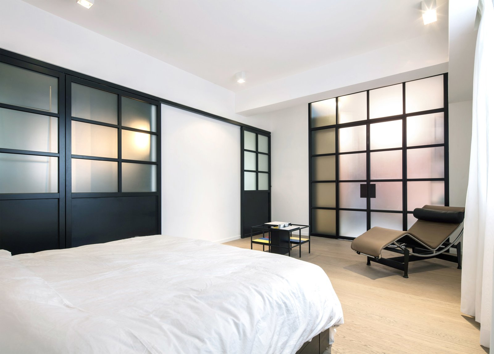 Tagged: Bedroom, Chair, Ceiling Lighting, Bed, and Light Hardwood Floor.  Photo 5 of 7 in See How This Colorful Hong Kong Apartment Was Made to Feel Bigger Than it Actually Is