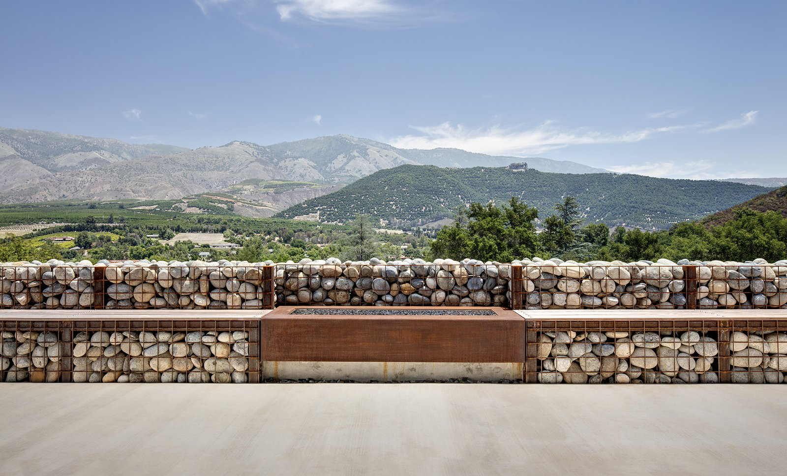 The gabions hold smooth rocks from the nearby San Luis Rey River; a fireplace feature is flanked by benches. Tagged: Walkways, Outdoor, Front Yard, Stone Patio, Porch, Deck, Concrete Patio, Porch, Deck, Metal Patio, Porch, Deck, and Vertical Fences, Wall.  Photo 5 of 5 in Mountain Song