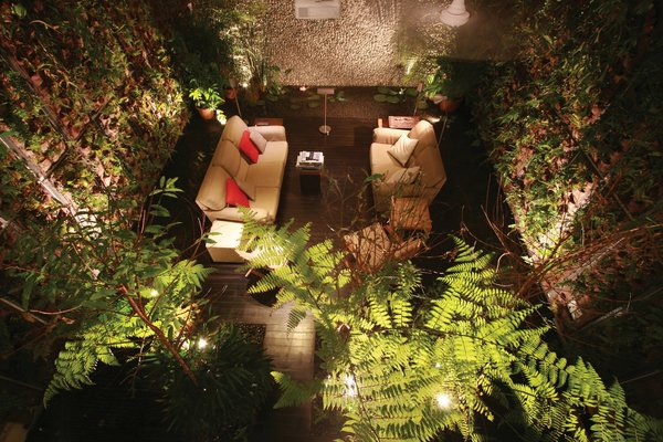 Modern home with sofa, ceiling lighting, front yard, dark hardwood floor, living room, trees, wood patio, porch, deck, and metal tread. Photo 4 of Tree House at Jalan Elok