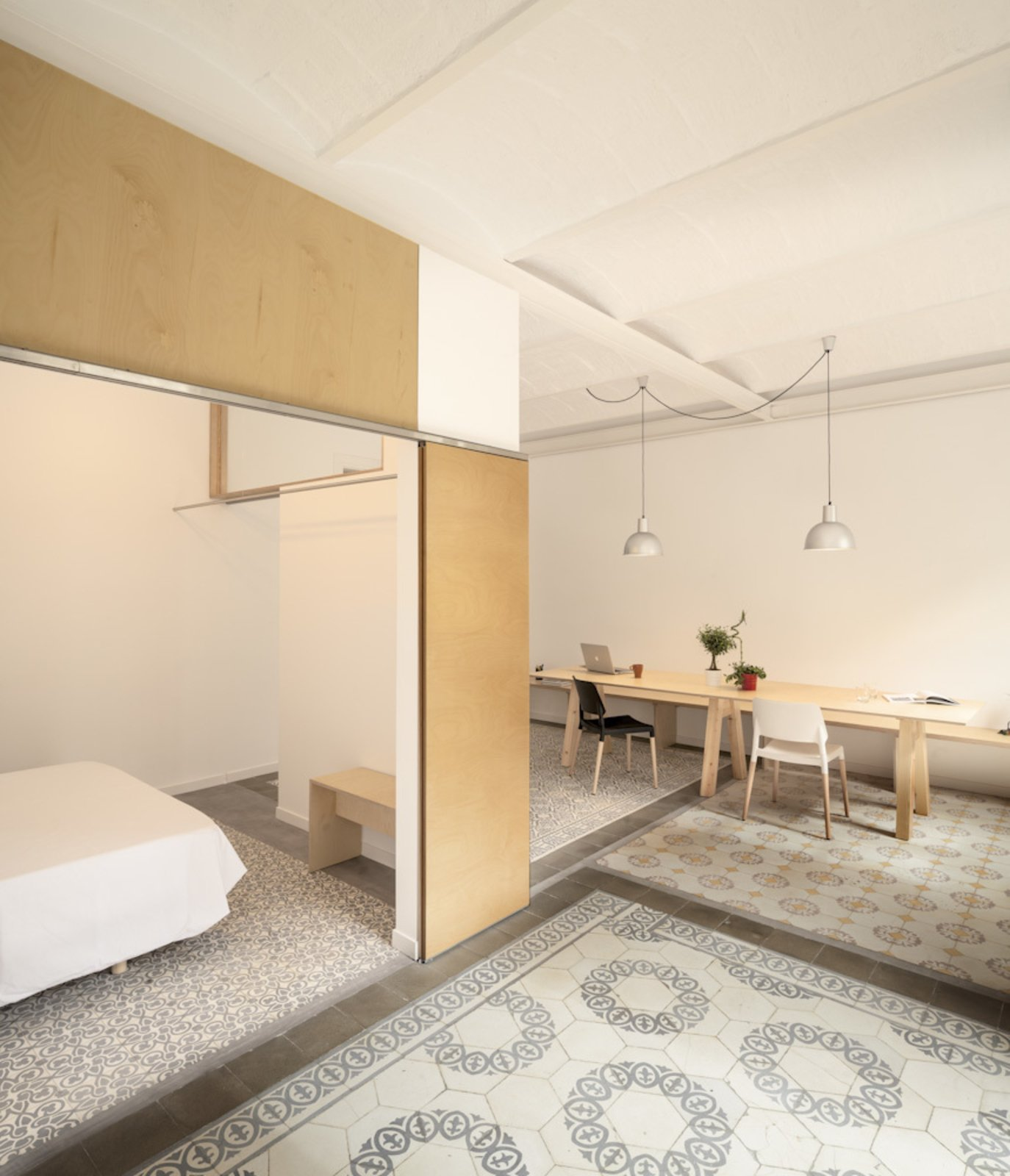 A renovated apartment in the Catalan city of Barcelona preserved the existing historic cement tiles, which maintains the original room layout in the home.  Photo 3 of 13 in 11 Examples of How to Incorporate Traditional Building Materials Into Your Modern Home