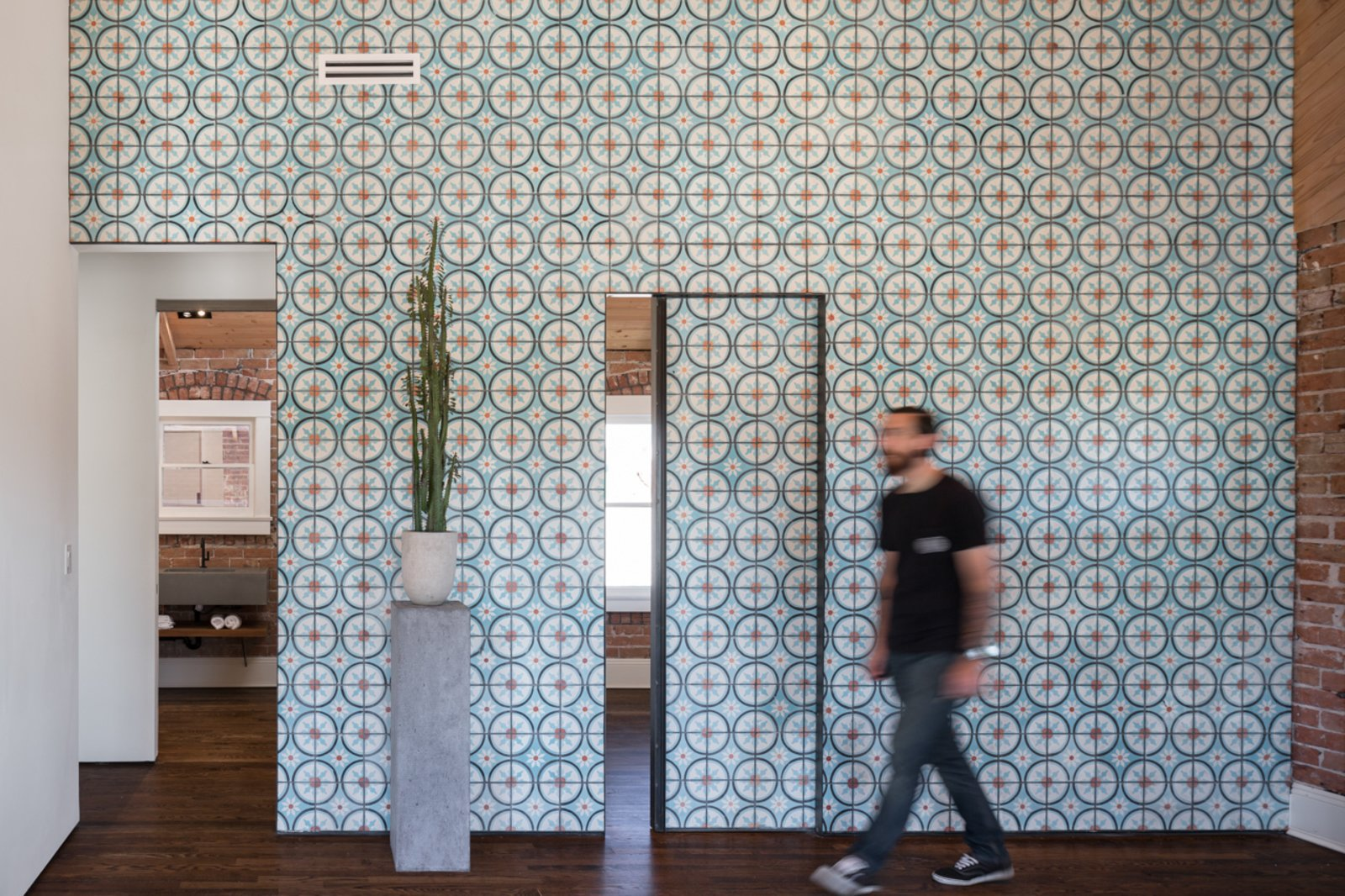 Off the living room, two small bedrooms and a bathroom can be reached through sliding doors that, when closed, continue the cheerful pattern of the Moroccan cement tiles covering the wall.  Photo 5 of 13 in 11 Examples of How to Incorporate Traditional Building Materials Into Your Modern Home