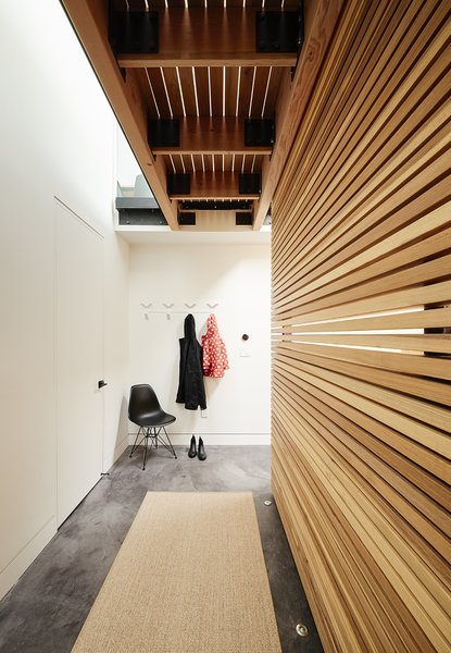 The lower level is distinguished by stained concrete flooring. In the hallway,  a Molded Plastic Chair by Charles and Ray Eames for Herman Miller offers a place for the residents  to remove their coats and shoes.  The seat has an Eiffel base.