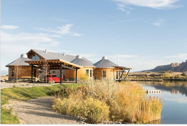 """Modern home with front yard, shrubs, outdoor, and grass. When Colorado homeowners wanted a series of tent yurts for their vacation home, architect Rick Dominick suggested these more durable """"yurt-inspired"""" structures instead, in order to weather the harsh climate—which can often reach into the hundreds during the summer and experience high winds all year long. Photo 2 of Yurt-Inspired Home on the Range"""