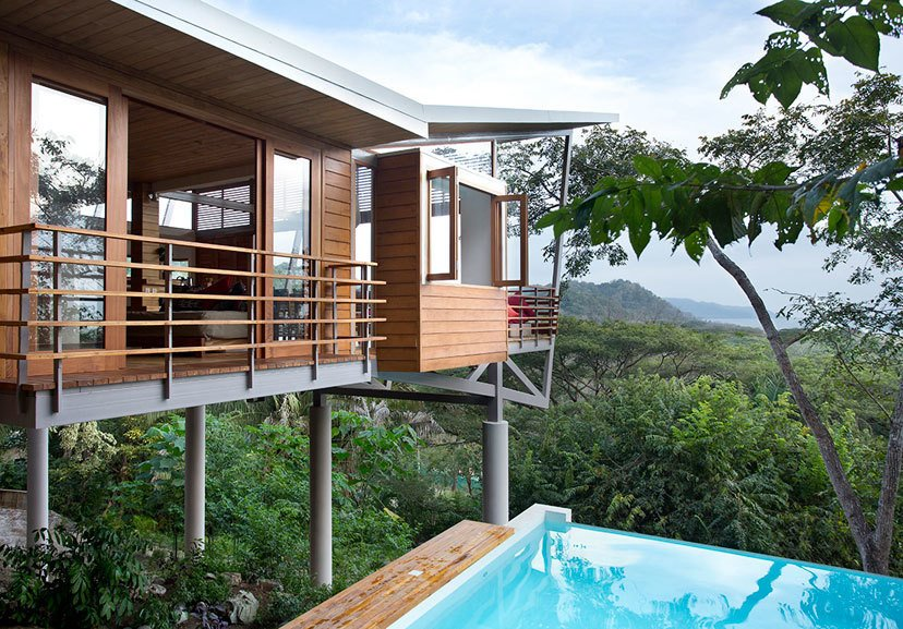 The Floating House stands above the jungle canopy of Costa Rica and was designed by architect Benjamin Garcia Saxe. It's a short walk to the beach and offers elegance that's rooted in nature and simplicity. The structure is made up of three pods that are connected by elevated, outdoor bridges and walkways. Teak flooring and furniture add natural warmth to the main living areas, which are connected to two upstairs bedrooms and an open-air spa bathroom via a 78-foot walkway. The home also features a lounge framed by Concertina floor-to-ceiling glass doors with expansive views of the ocean and jungle.