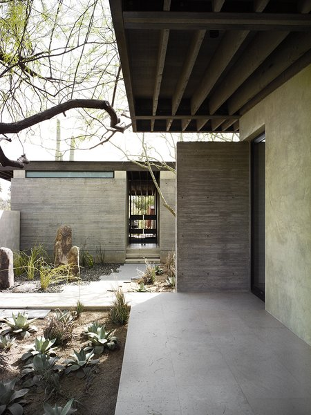 The Phoenix home of designers and builders Sarah Swartz Wessel and Ethan Wessel sits amid desert-friendly trees and plants. The couple bought the property in 1998 and worked on the house for a decade.