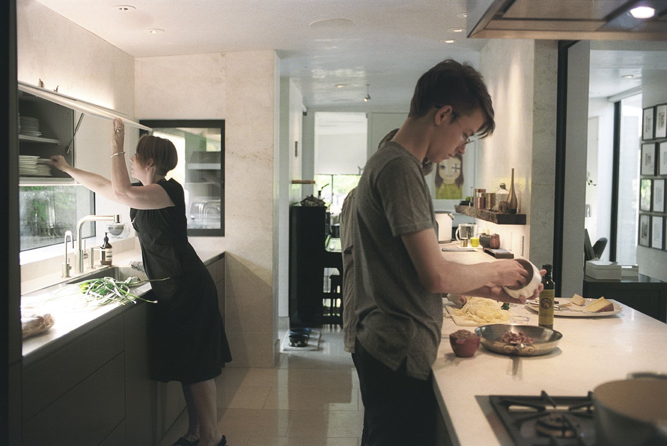 Sarah and her sons prepare a meal in the kitchen, which the Wessels recently upgraded with Bulthaup cabinets, counters, and sink. The stovetop is from Gaggenau and the faucet is from Dornbracht. On the far wall is one of Yoshitomo Nara's signature eye-patch portraits. Tagged: Kitchen, Range, White Cabinet, Cooktops, Drop In Sink, and Porcelain Tile Backsplashe.  Photo 4 of 15 in In Praise of Shadows