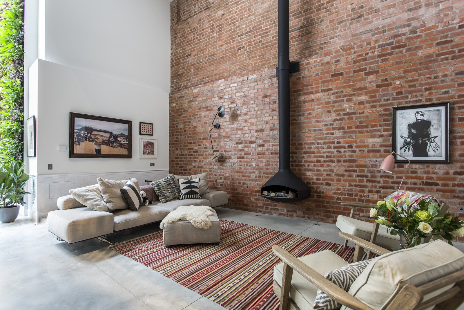 A former cooperage in Clerkenwell where barrels for a local brewery were made, this four-bedroom conversation by Chris Dyson Architects now is a chic holiday rental property. Tagged: Living Room, Hanging Fireplace, Concrete Floor, Chair, and Sofa.  Photo 2 of 11 in 10 Modern Homes in London