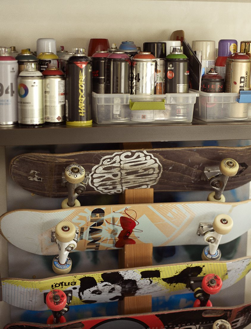 In the music room, skateboards are stored below spray paints the family and friends use to decorate the skate bowl. Tagged: Concrete Counter, Den, Chair, Ceiling Lighting, Garden, Gardens, Flowers, Concrete Floor, Vegetables, and Storage Room. Wessel Residence by Dwell