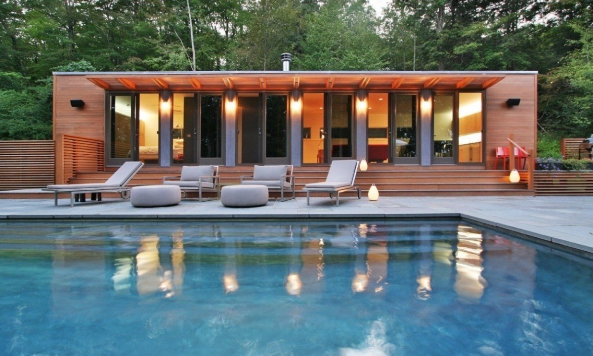 This pool house in Connecticut was fashioned from two shipping containers, bedecked in well-lit cedar, which contrasts beautifully with the blue of the water.  Photo 7 of 10 in 10 Sunny Poolside Prefabs