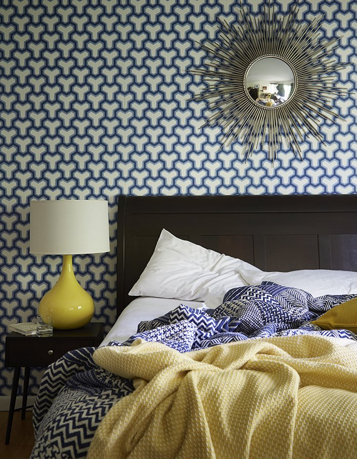 A sunburst mirror, which George bought on eBay, pops against patterned Antonina Vella wallpaper in the guest bedroom. The lamp is vintage. Tagged: Bedroom, Night Stands, Table Lighting, and Bed.  Photo 13 of 13 in How to Update a Midcentury Modern Gem